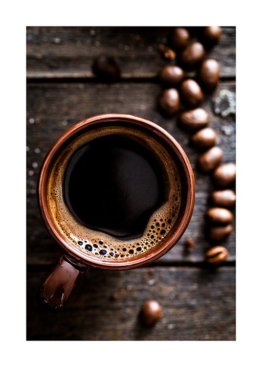 – Photograph from above of a cup of coffee on a wooden table, with coffee beans on the side