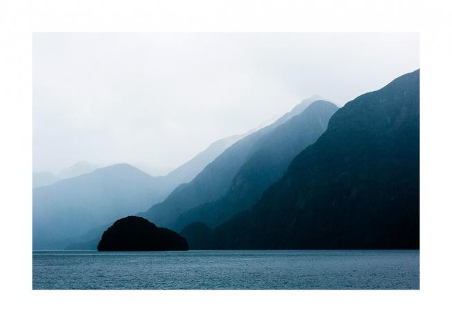 - Photograph of sea in front of blue mountains in layers with fog behind them