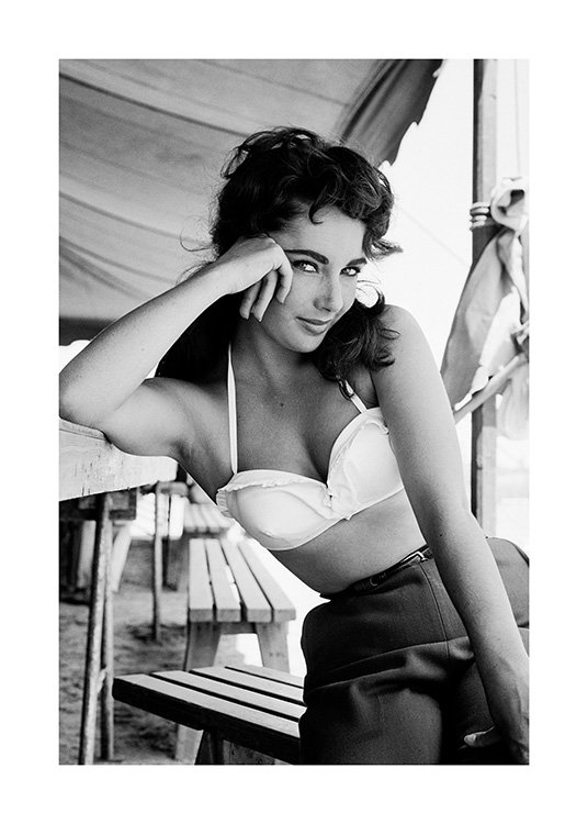 - Black and white photograph of Elizabeth Taylor in a bikini top and shorts with her hand against her cheek