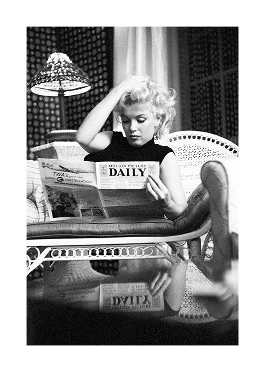 – Black and white photograph of the icon Marilyn Monroe while she's reading a newspaper on the sofa