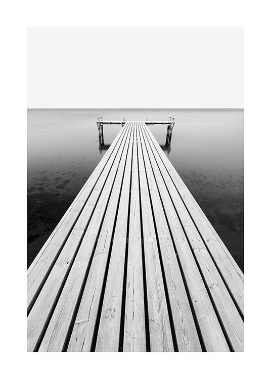 – Black and white photograph of an ocean with a jetty leading into the water