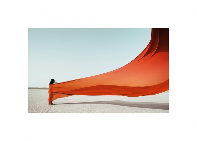 - Photograph of a woman wrapped in an orange fabric flowing in the wind, with a light blue background