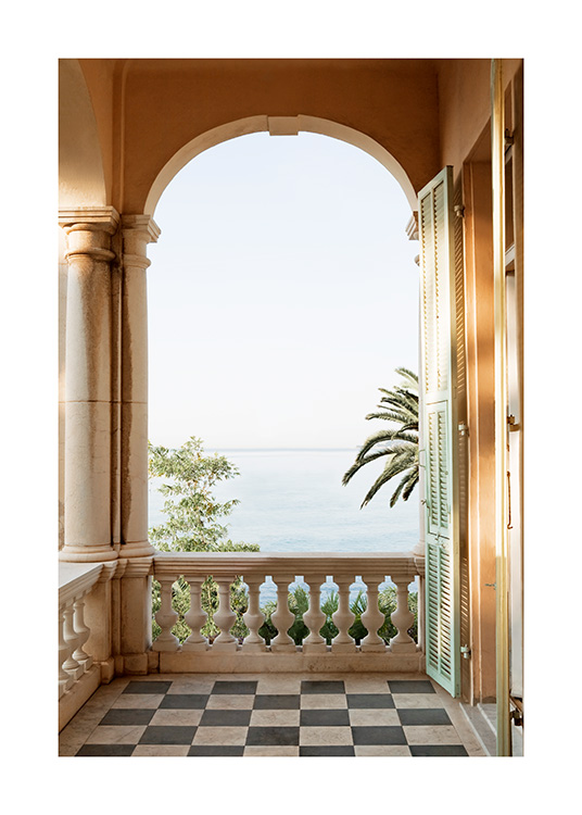 – Photograph of an arch on a balcony with palm trees and the ocean in the background