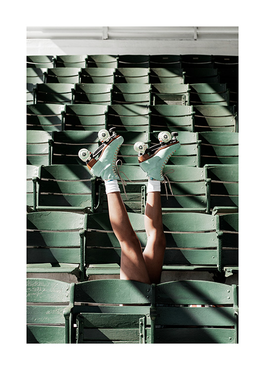 – Photograph of a person wearing roller skates stretching their legs up between green seats at a stadium