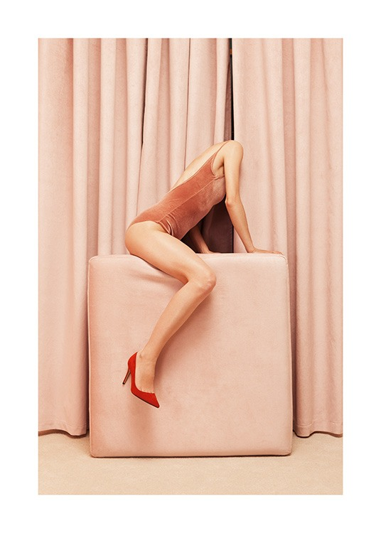 – Photograph of a woman sitting on a beige cushion, wearing a velvet body and red high heels