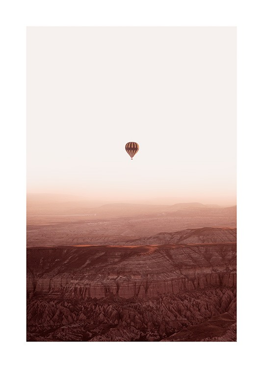 – Photograph of a mountain landscape with an air balloon flying over it