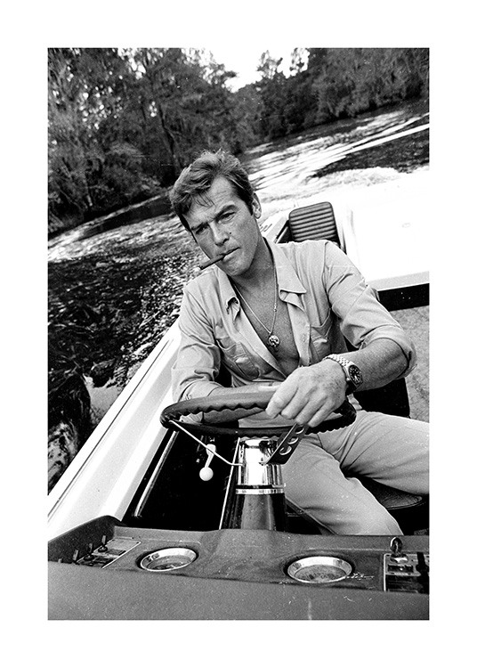 – Black and white photograph of Roger Moore driving a boat with a cigarette in his mouth