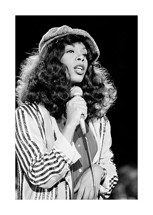 – Black and white photograph of Donna Summers, wearing a hat and striped shirt, holding a microphone