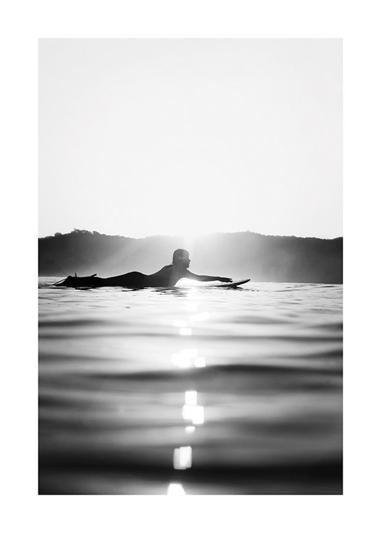 – Black and white photograph of a surfer laying on a surfboard in the water