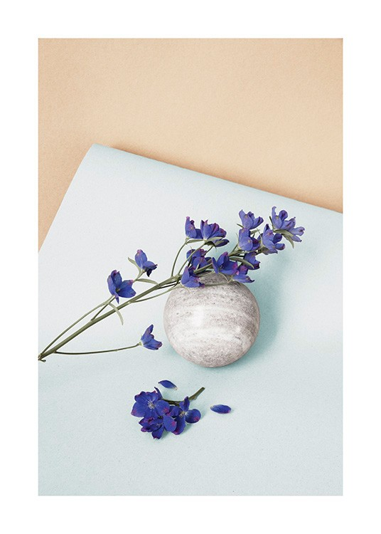 – Photograph of a purple flower and purple petals laying on a grey stone ball on light blue paper