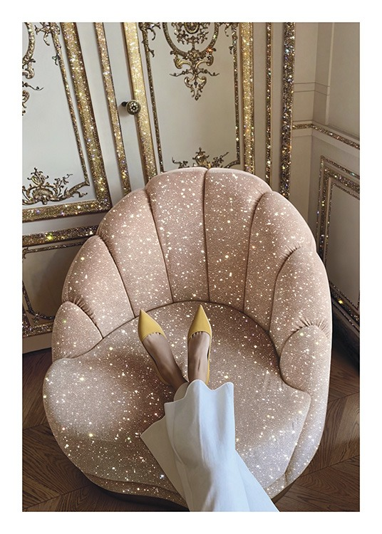 – Photograph of a pink, sparkling chair in front of a gold and white wall, with a woman resting her feet on the chair