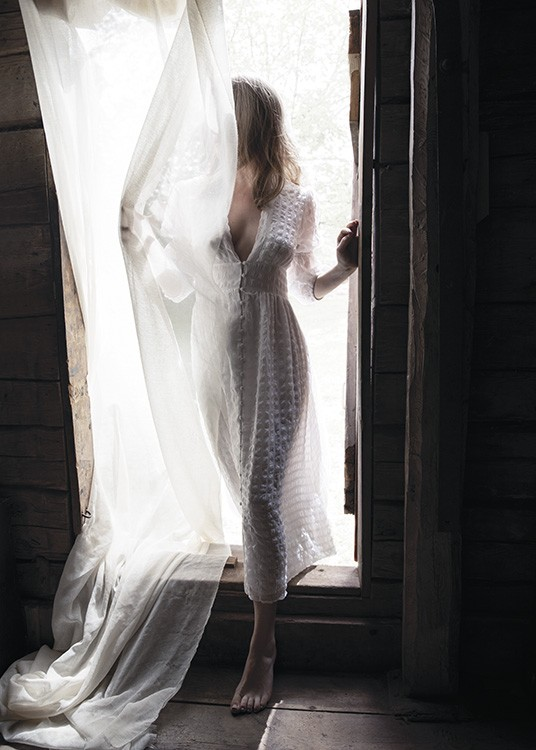 – Photograph of a woman sin a doorway in a white dress, covered by a white curtain