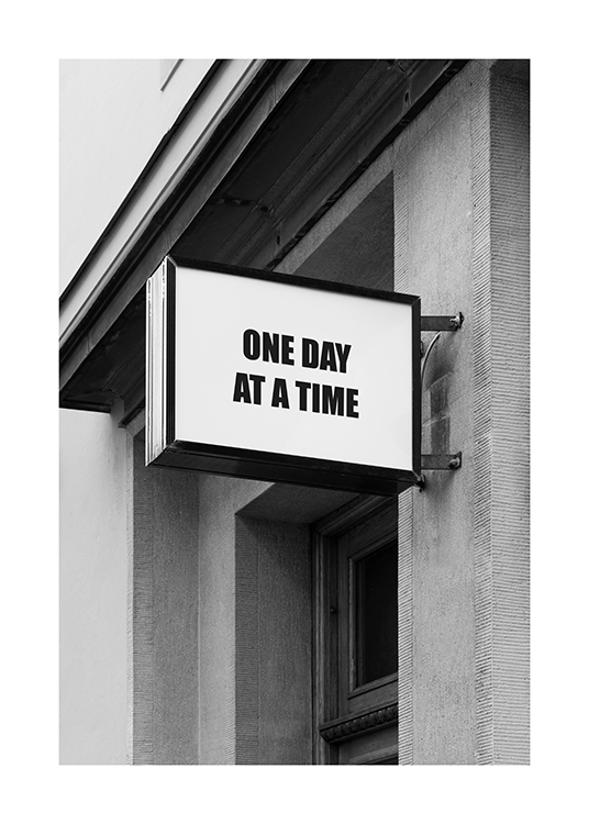 – Black and white photograph of a sign with text on a building